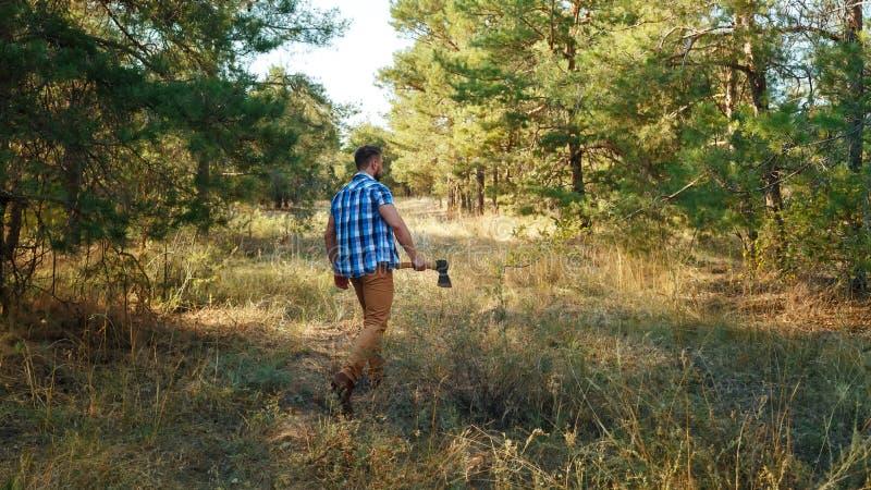 Skogsarbetaren är i träna som rymmer yxan arkivfoto