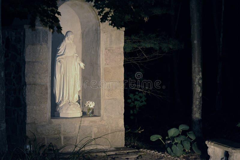 Skogsbevuxen utomhus- relikskrin som fostrar Mary på natten royaltyfri fotografi