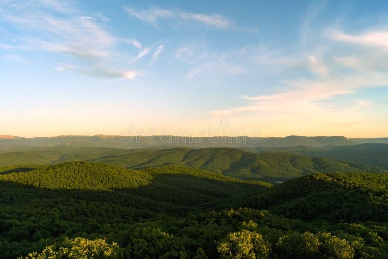 Skogsbevuxna berg på solnedgången royaltyfria bilder