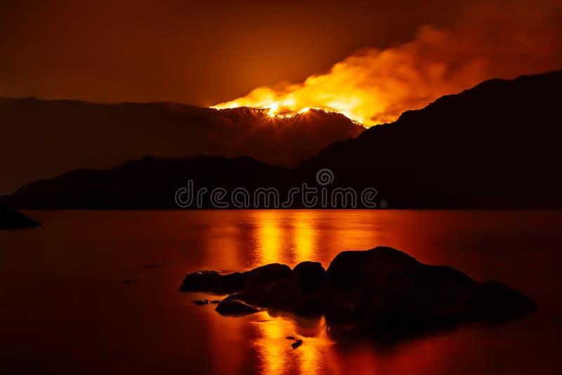 Skogsbrand på natten som reflekterar i den närliggande sjön royaltyfria bilder