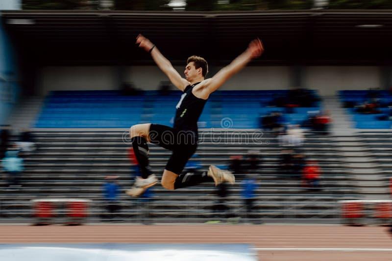 Skok w dal męskiej atlety zamazany ruch obraz royalty free