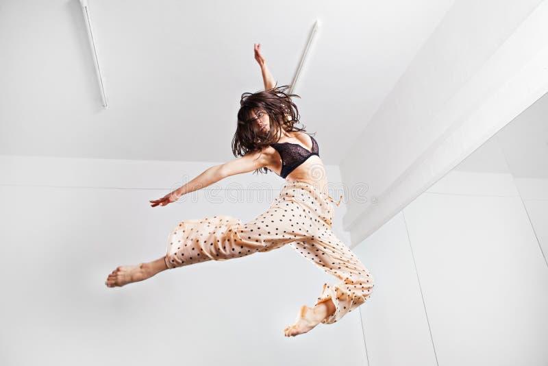 Skokowa młoda kobieta na trampoline zdjęcie stock