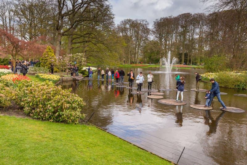 Skokowi ludzie w th drylują sposób w wodzie w parku przy Keukenhof fotografia stock