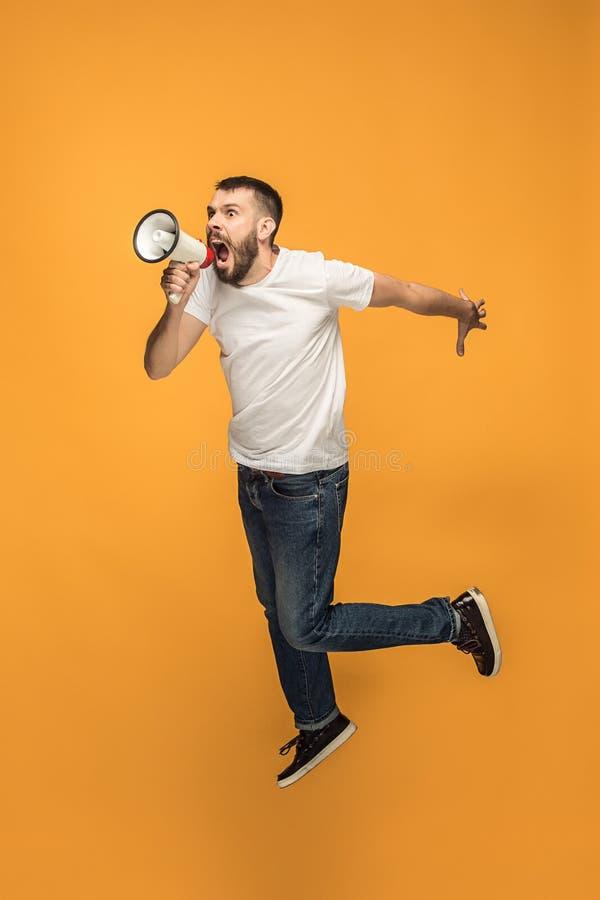 Skokowy fan na pomarańczowym tle Młody człowiek jako piłki nożnej fan piłki nożnej z megafonem obraz royalty free
