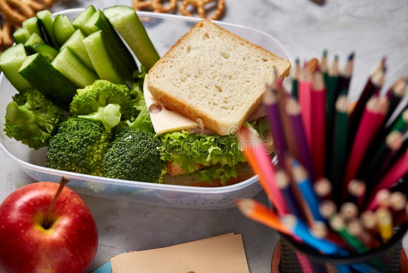 Skola- eller picknicklunchask med smörgåsen och olika färgrika grönsaker och frukter på träbakgrund, slut upp royaltyfri fotografi