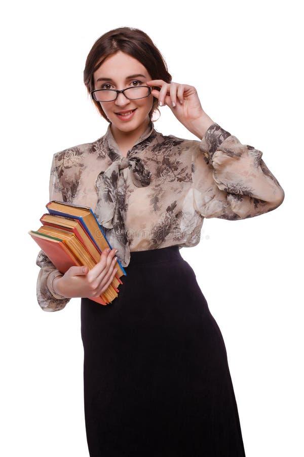 Skola flickalärarkandidatkvinnan i exponeringsglas med böcker royaltyfria foton