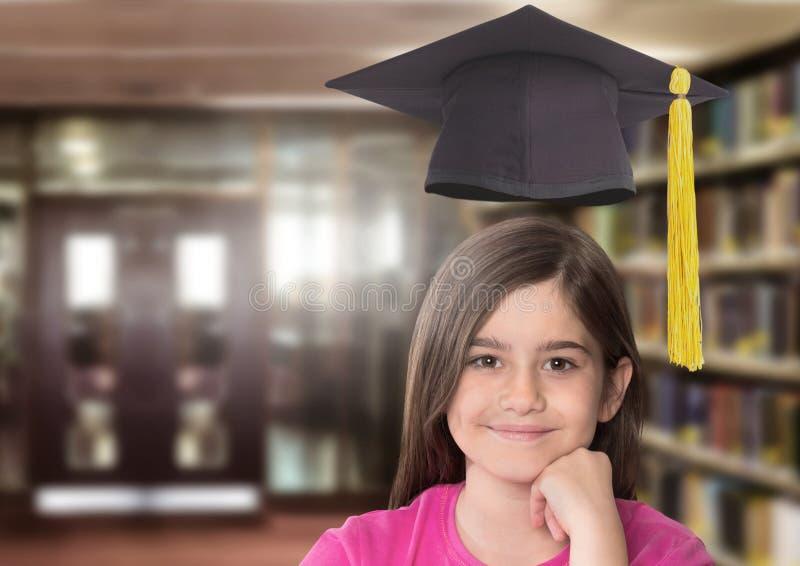 Skola flickan i utbildningsarkiv med avläggande av examenhatten royaltyfri fotografi