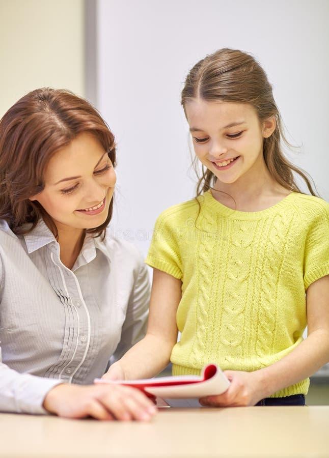 Skola flickan med anteckningsboken och läraren i klassrum arkivfoton