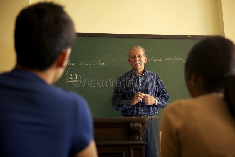 Skola folk, professorn som talar till studenter under kurs i Co arkivbild