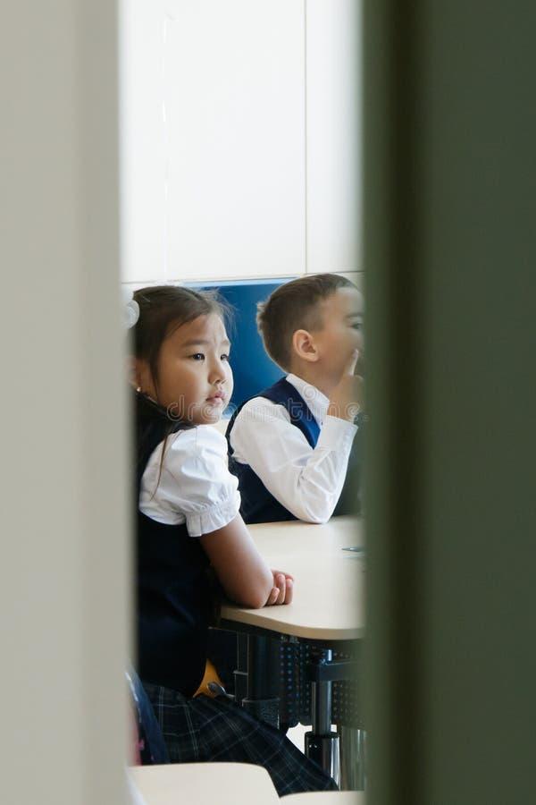 skola Halvöppna dörrar av klassrumet Det kan ses hur flickan och pojken i skolalikformig sitter på skrivbordet och lyssnar uppmär fotografering för bildbyråer