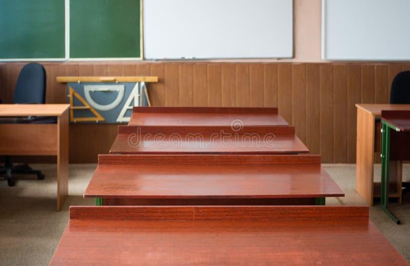 Skola klassrumet med den skolaskrivbord och svart tavla i högstadium arkivbilder