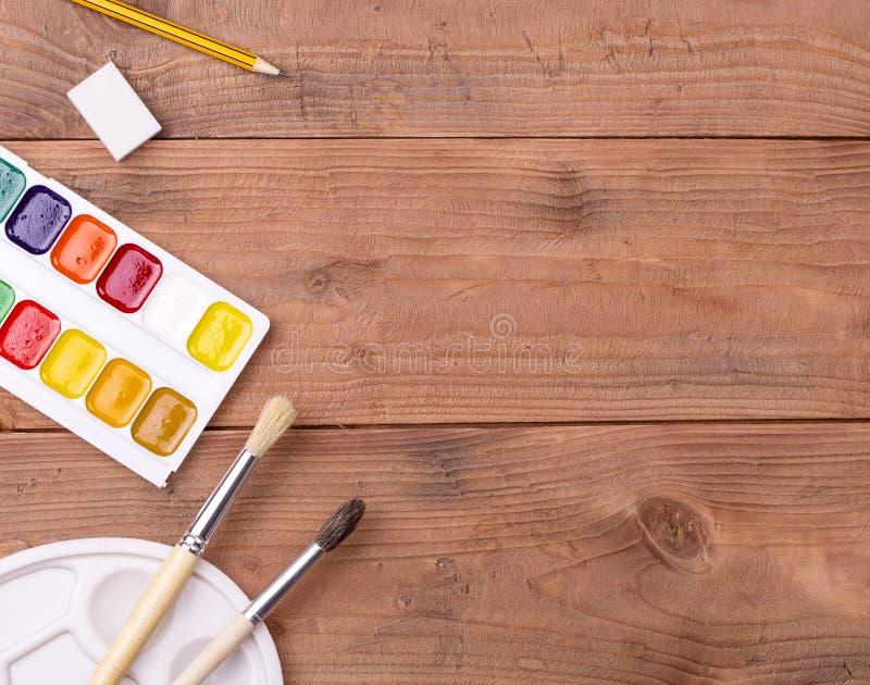 Skola- och målaretillbehör på trätabellen royaltyfri fotografi