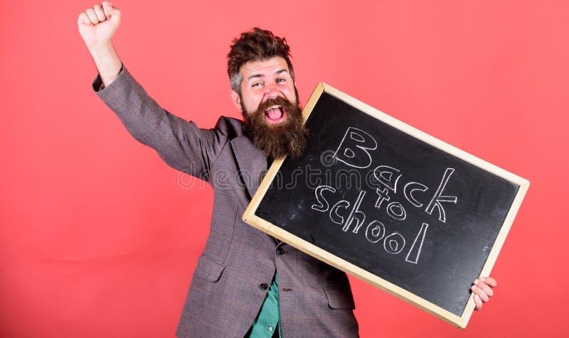 Skola och studerabegrepp Läraren välkomnar studenter medan svart tavlainskriften för håll tillbaka till skolan positivt fotografering för bildbyråer