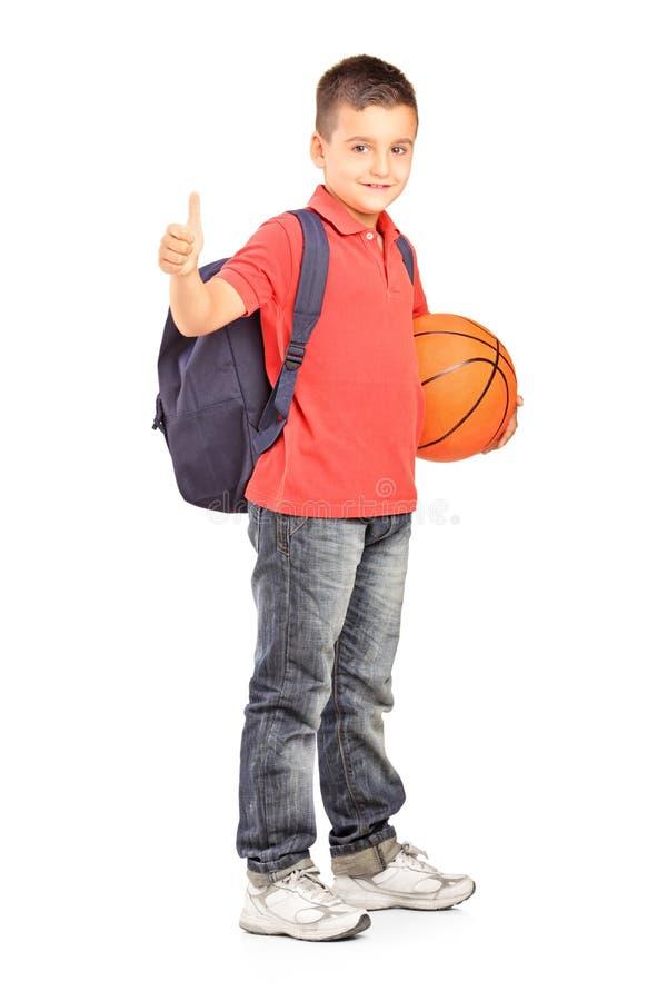 Skola pojken med ryggsäckinnehav en basket och att ge en tum royaltyfri foto