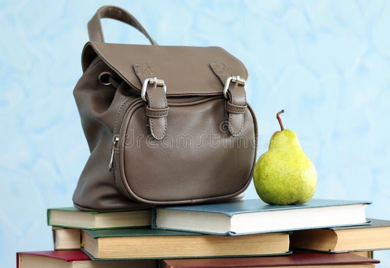 Skola ryggsäcken med böcker och päronet, närbild arkivfoto