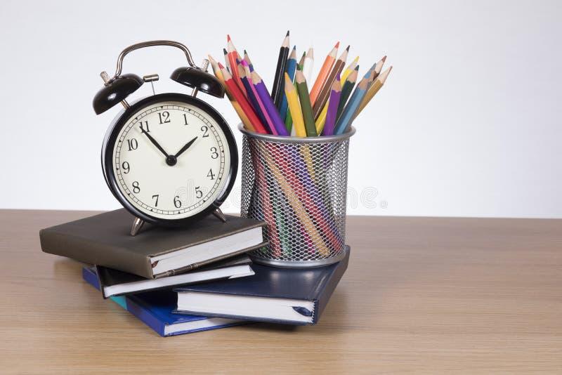 Skola som lär böcker, blyertspennor och ringklockan arkivbild