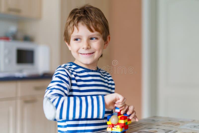 Skola ungepojken som spelar med massor av litet färgrikt plast- kvarter arkivbild