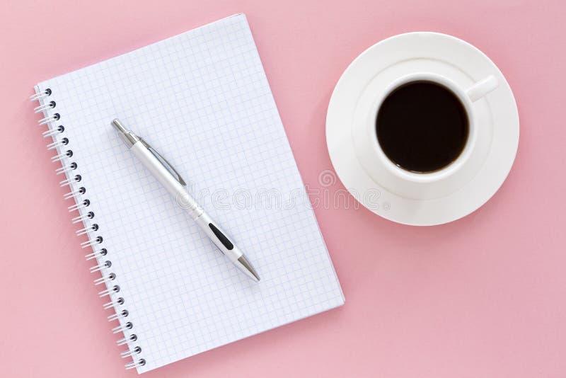 skolaanteckningsbok p? en rosa bakgrund Vit sida för mellanrumsnotepad, penna och kaffe, färgbakgrund Top besk?dar arkivbilder