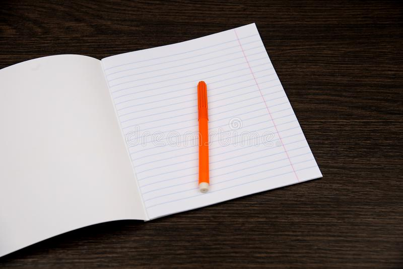 Skolaanteckningsbokpapper orange mark?rer Anteckningsbok i linje och blyertspenna ?ppen anteckningsbok p? en brun bakgrund planl? arkivbild