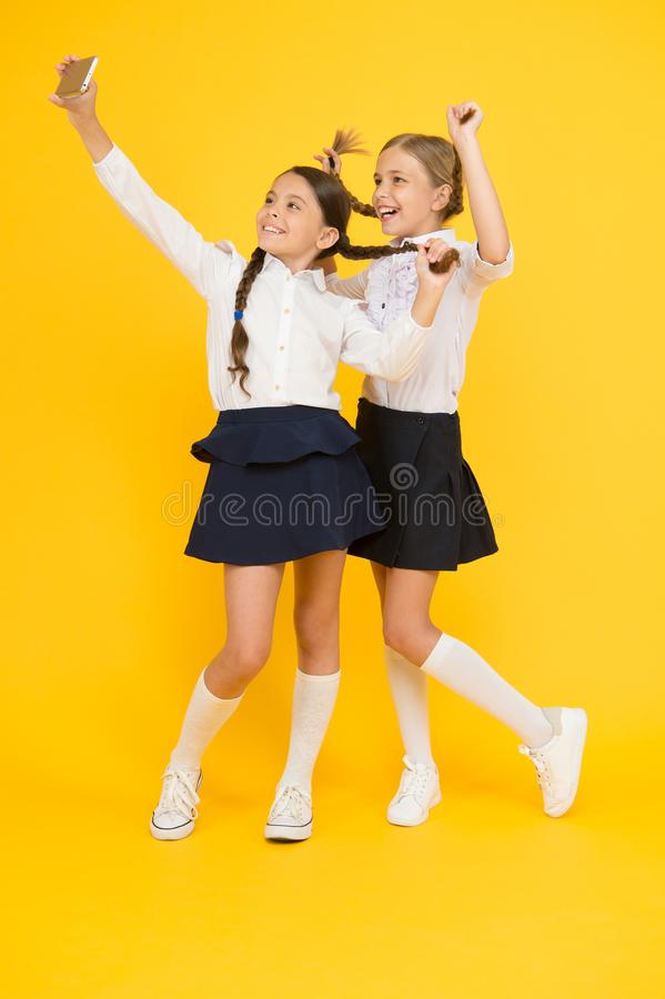 Skolaavbrott Deltagaren av den h?ga gruppen f?r de f?rsta kursungarna lyckliga vänner med smartphonen ungar gör selfiefotoet, kam arkivbilder
