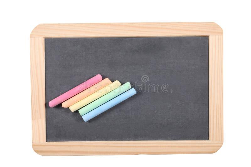 Skolabegrepp: stäng sig upp på en kritiserasvart tavla med chalks som isoleras på vit bakgrund och den snabba banan arkivfoton