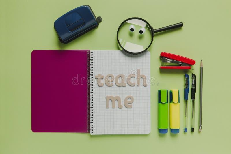 Skolabegreppet med ` undervisar mig `-bokstäver som göras med trä, på en anteckningsbok royaltyfria foton