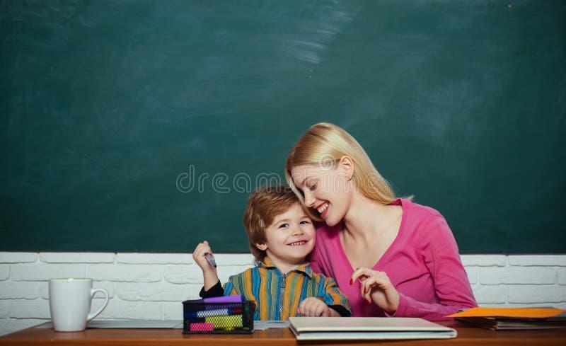Skoladagis och utveckling Barnav?rd och framkallning F?rskole- f?rberedelse Ungepys och lärarekvinna arkivfoton