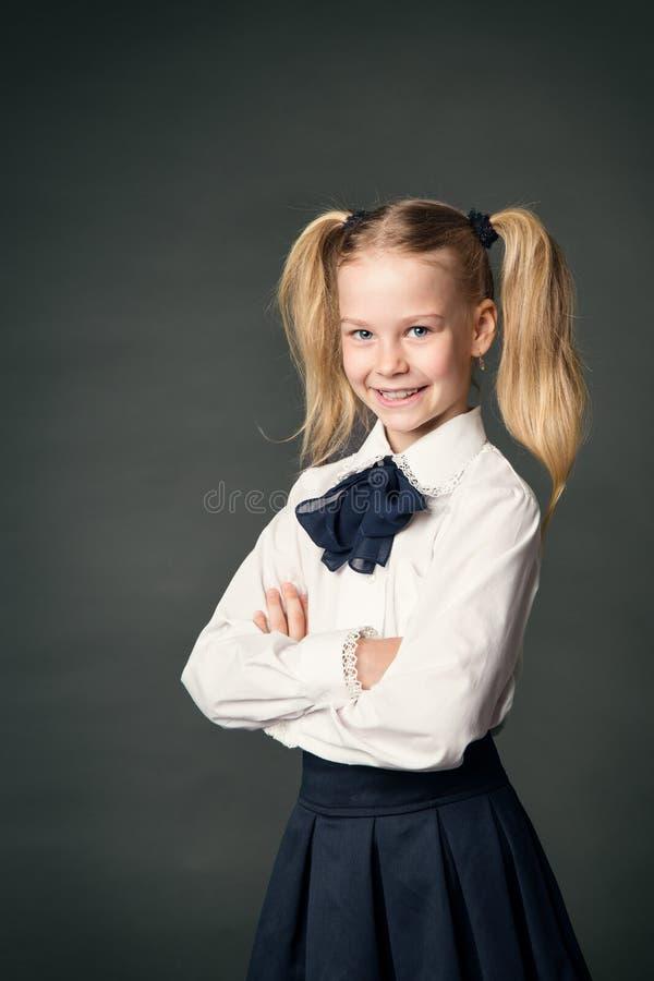 Skolaflicka över svart tavlabakgrund, lycklig barnstående fotografering för bildbyråer
