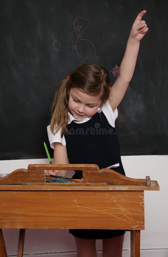 Skolaflicka på skrivbordet arkivfoto