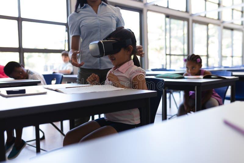 Skolaflicka som använder virtuell verklighethörlurar med mikrofon på skrivbordet i klassrum arkivbild