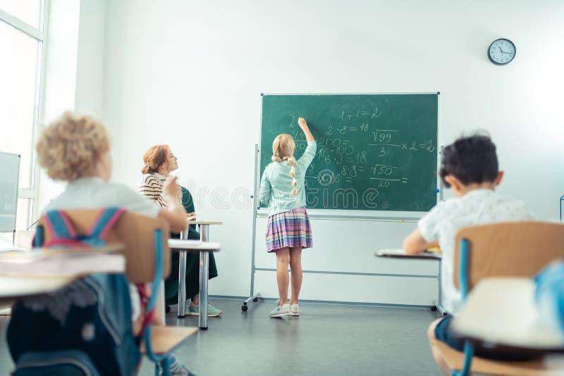 Skolaflicka som framme talar och skriver av gruppen arkivbild