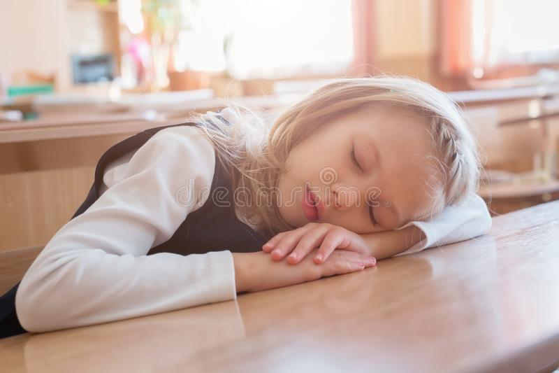 Skolaflickan som sover på skolan, är sömn på skrivbordet Student Studera för elev royaltyfri foto