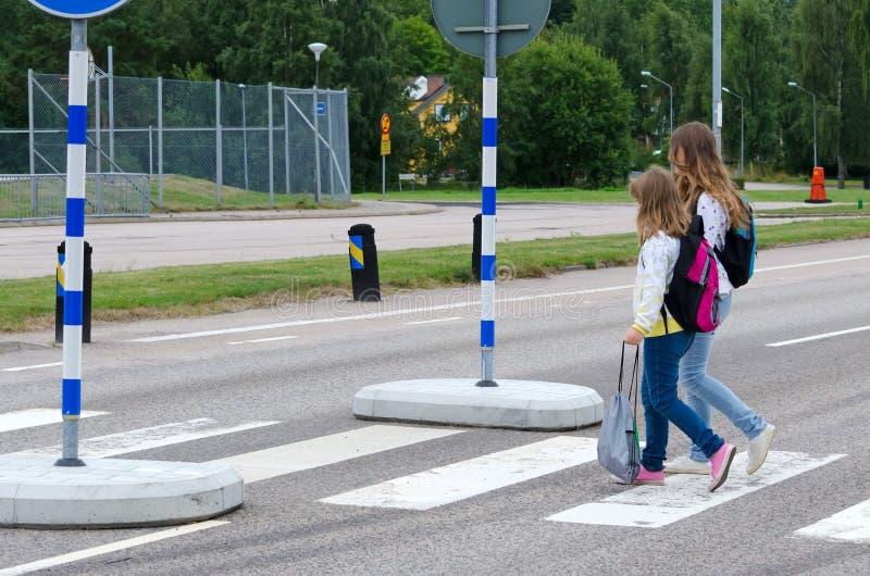 Skolaflickor på sebratvärgatan fotografering för bildbyråer
