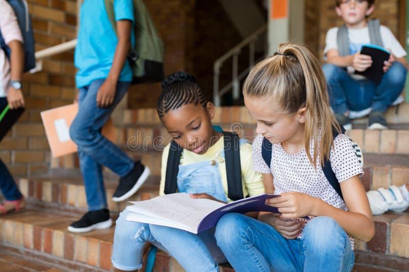 Skolaflickor som tillsammans studerar efter skola arkivbilder