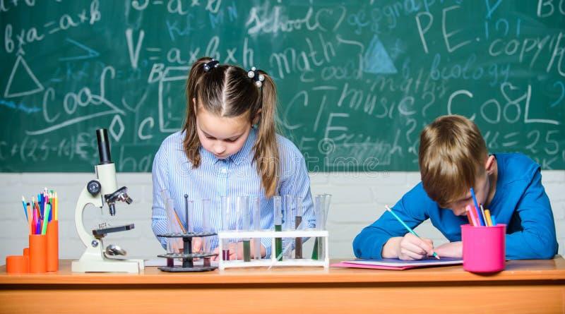 Skolakemikurs Skolalaboratorium F?r smarta studenter f?r flicka och f?r pojke skolaexperiment Beskriva kemiskt arkivfoto