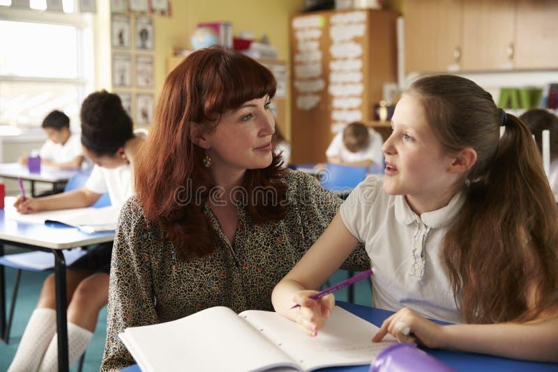 Skolalärare som hjälper upp en flicka på hennes skrivbord i grupp, slut arkivbild