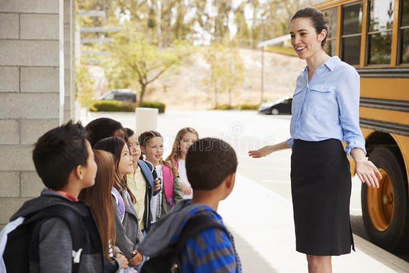 Skolalärare som talar till ungar, för de får på skolbussen royaltyfri foto