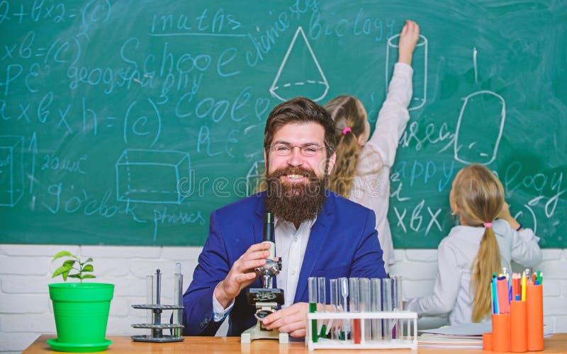 Skolal?rare av biologi Sk?ggigt l?rarearbete f?r man med mikroskopet och provr?r i biologiklassrum Biologilekar arkivfoto