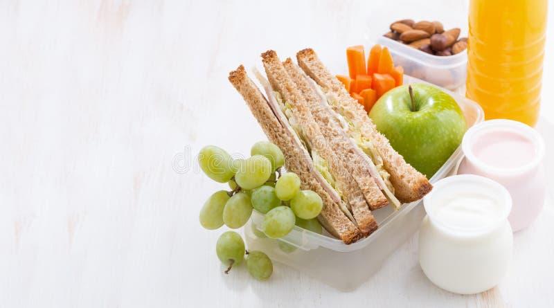 Skolalunch med smörgåsar, frukt och yoghurt arkivfoto