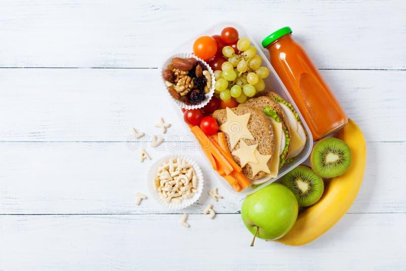 Skolalunchask med grönsaker, frukter och smörgåsen för sunt mellanmål på den vita träbästa sikten för tabell royaltyfri fotografi