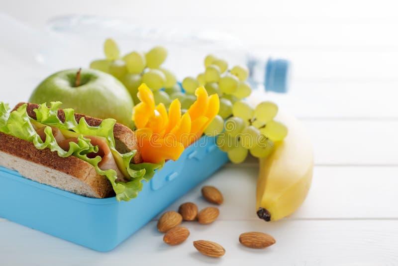 Skolalunchask med smörgåsen, äpplet, söt peppar, druvan och flaskan av vatten på den vita trätabellen arkivfoto