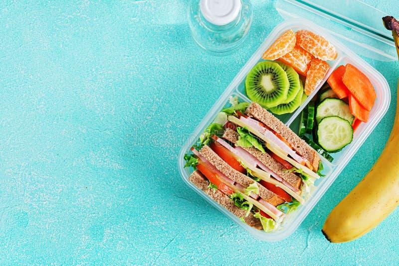 Skolalunchask med smörgåsen, grönsaker, vatten och frukter på tabellen arkivfoto