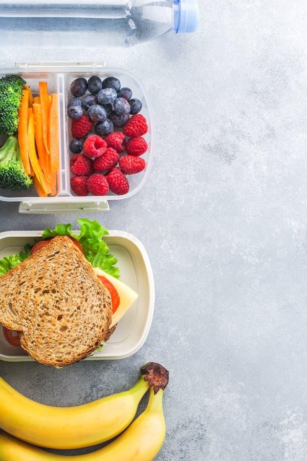 Skolalunchasken med mandlar för smörgåsgrönsakvatten och frukter på grå färger bordlägger sunt royaltyfri foto