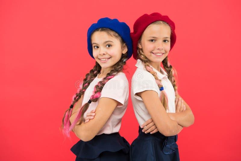 Skolamodebegrepp Skolflickor bär formella likformig- och baskerhattar Elitskolahögskola Utbildning utomlands applicerar royaltyfri fotografi