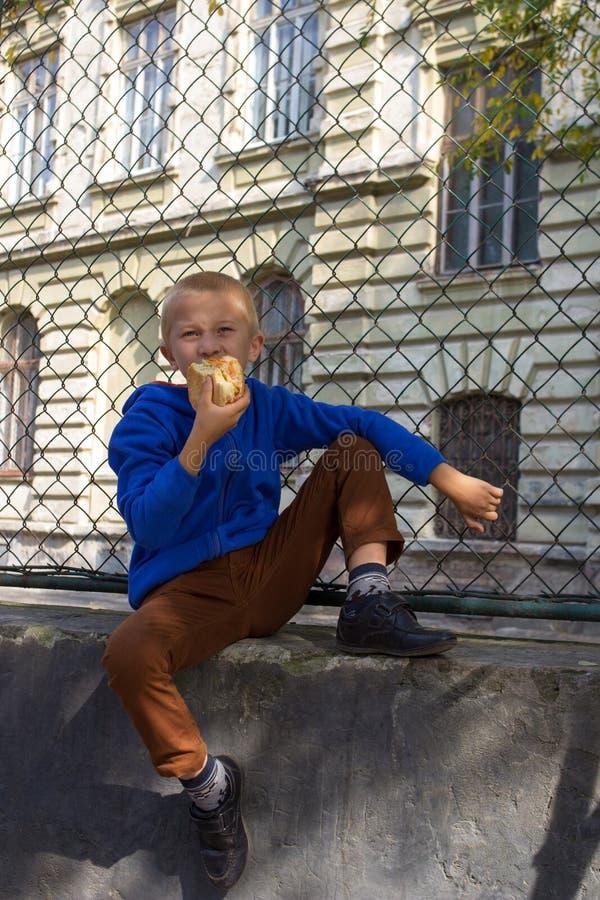 Skolan är en pojke med en hamburgare royaltyfri fotografi