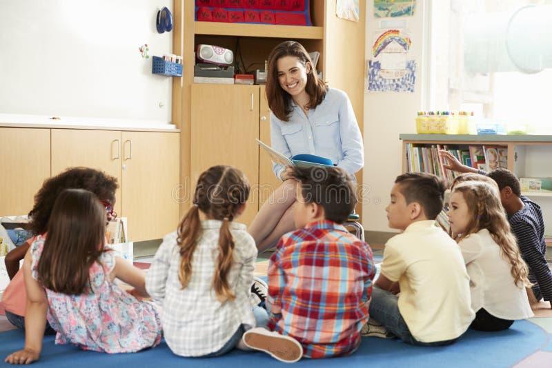 Skolan lurar sammanträde på golv framme av läraren, låg vinkel arkivbild