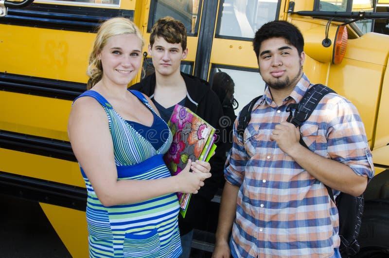 Skolan lurar stående framme av bussen royaltyfri foto
