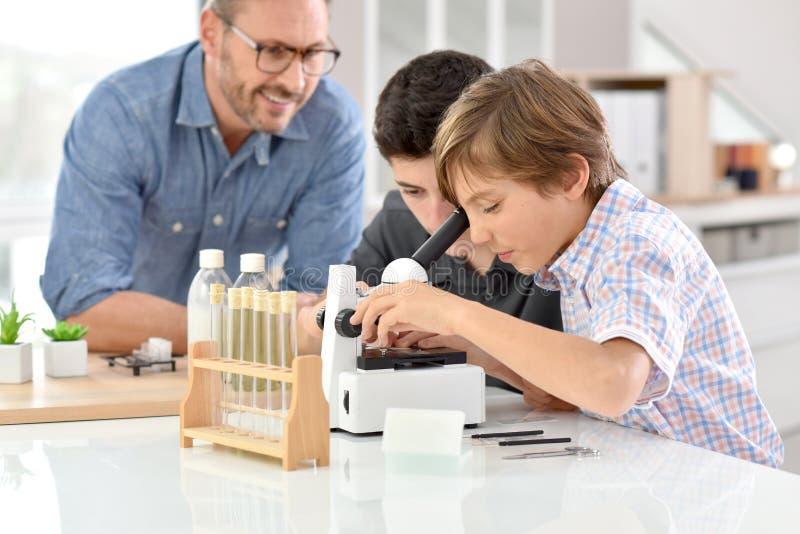 Skolapojkar i kemigrupp med läraren arkivbilder