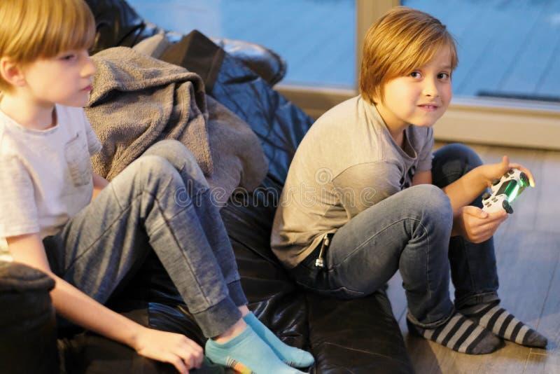 Skolapojkar spelar på golvet i ett hus royaltyfria foton