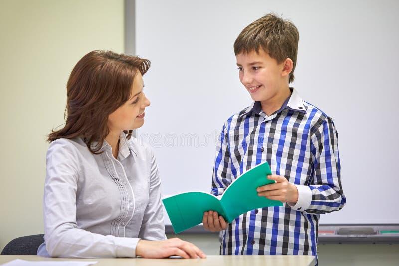 Skolapojke med anteckningsboken och läraren i klassrum arkivbild